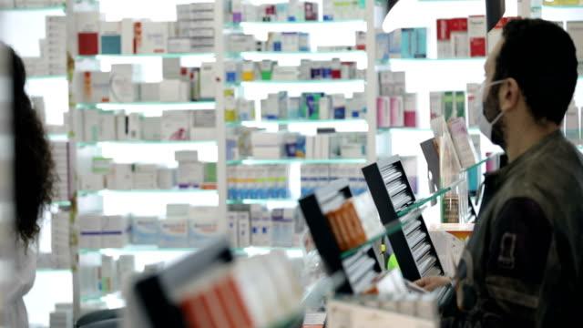il farmacista donna che indossa una maschera chirurgica dice al paziente maschio che indossa una maschera chirurgica come usare la sua medicina - farmacia video stock e b–roll
