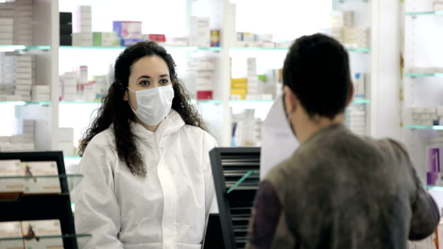 vídeos de stock, filmes e b-roll de farmacêutica usando máscara cirúrgica diz ao paciente do sexo masculino que usa uma máscara cirúrgica como usar seu remédio - luvas