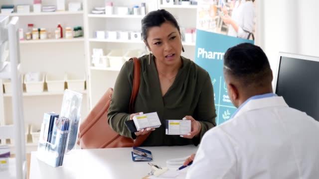 vídeos y material grabado en eventos de stock de la cliente ala de farmacia femenina le pide consejo a un farmacéutico masculino sobre los medicamentos de venta libre - receta médica medicamento