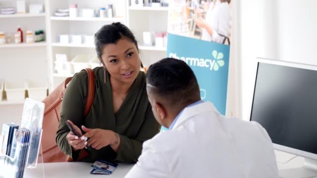 vídeos de stock e filmes b-roll de female pharmacy customer asks pharmacist about the pharmacy's mobile app - medicamento de prescrição