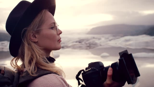 female photographer at glacier lagoon. sunset - photographer stock videos & royalty-free footage