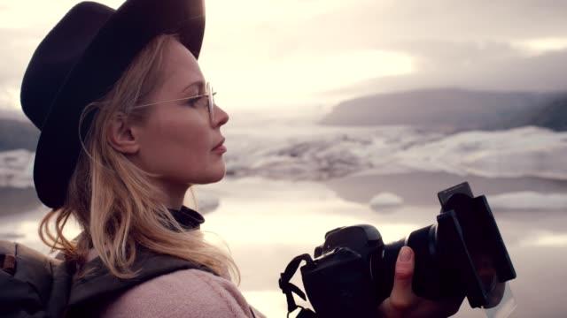 female photographer at glacier lagoon. sunset - fotografo video stock e b–roll