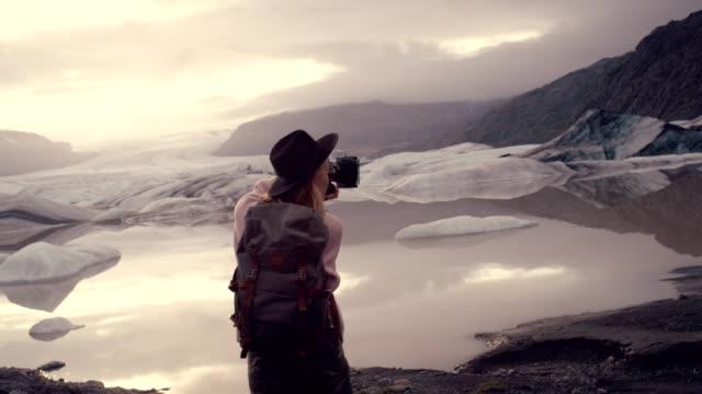 female photographer at glacier lagoon. sunset - artist stock videos & royalty-free footage