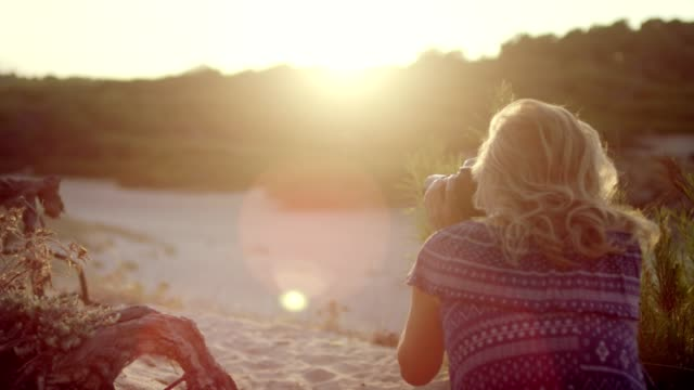 female photographer at the beach. sunset - femininity photos stock videos & royalty-free footage