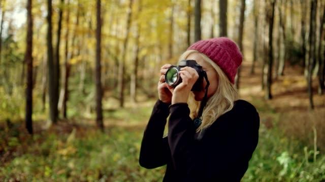 female photographer in autumn forest - fotografo video stock e b–roll