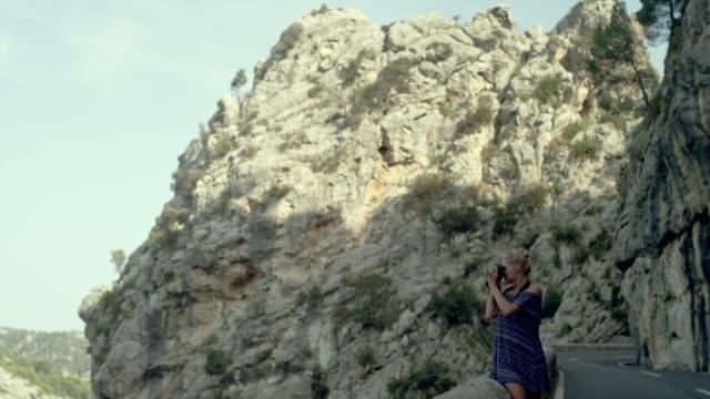 stockvideo's en b-roll-footage met vrouwelijke fotograaf omgeven door bergen. mooi landschap - druk spanning