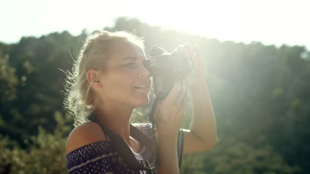 female photographer surrounded by mountains. beautiful landscape - femininity photos stock videos & royalty-free footage