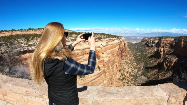 vídeos de stock e filmes b-roll de female photographer taking pictures of the canyon with her smartphone - temas fotográficos