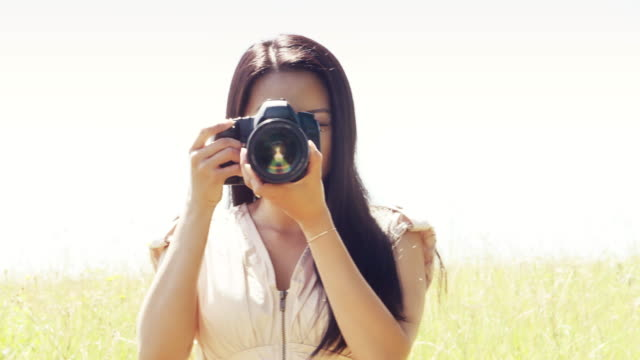 Female photographer using DSLR camera. Front view.