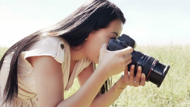 Female photographer using DSLR camera. Side view.