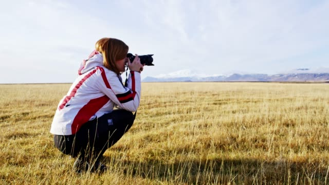 ms female photographer with camera photographing sunny remote landscape,iceland - see other clips from this shoot 31 stock videos & royalty-free footage
