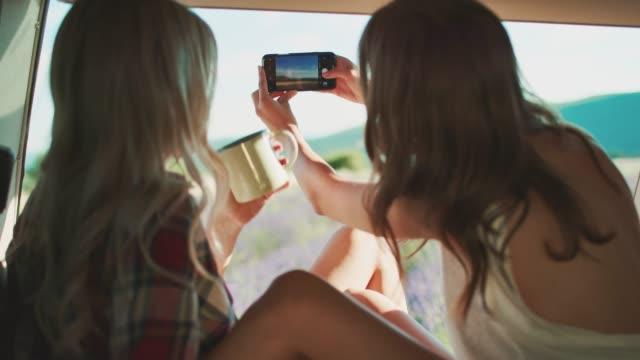 vídeos y material grabado en eventos de stock de mujeres fotografiando mientras acampan con un amigo - viaje por carretera