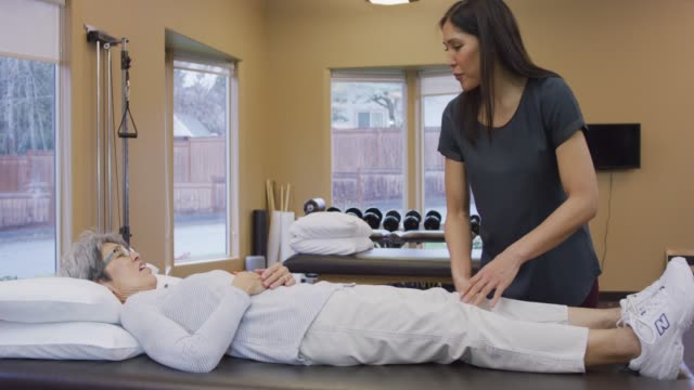 Female Physical Therapist Helping An Older Female Client Off of a Massage Table