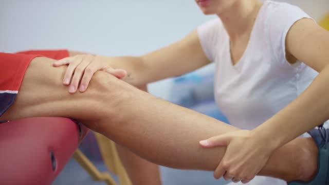 slo mo weibliche physiotherapeutin massiert das knie eines klienten, der auf dem massagetisch sitzt - massage table stock-videos und b-roll-filmmaterial