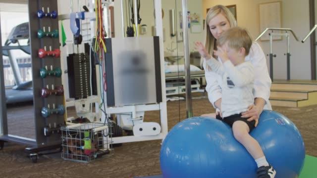 vídeos de stock, filmes e b-roll de feminino fisioterapeuta, trabalho com o jovem rapaz - physical injury