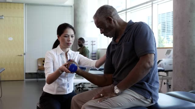female physical therapist works with senior man - hand weight stock videos & royalty-free footage