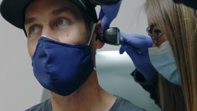 a female physician assistant (pa) wearing a surgical face mask uses an otoscope to look into the ears of a masked white man in his forties in an examination room in a medical clinic - medical examination room stock videos & royalty-free footage