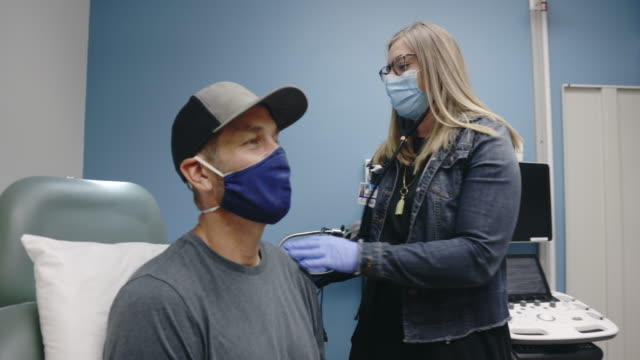 a female physician assistant (pa) wearing a surgical face mask walks into an examination room of a medical clinic, puts on her stethoscope, and begins listening to the lungs of a masked white male in his forties - medical examination room stock videos & royalty-free footage