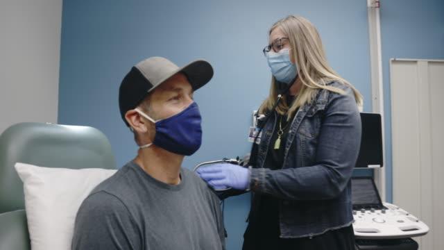 vidéos et rushes de une assistante médicale féminine (ap) portant un masque chirurgical marche dans une salle d'examen d'une clinique médicale, met son stéthoscope, et commence à écouter les poumons d'un mâle blanc masqué dans sa quarantaine - cabinet médical