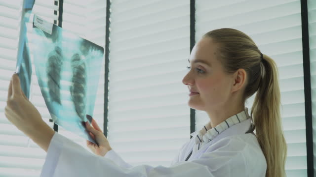 female physician reading x-ray and giving consultation to patient - scoliosis stock videos and b-roll footage