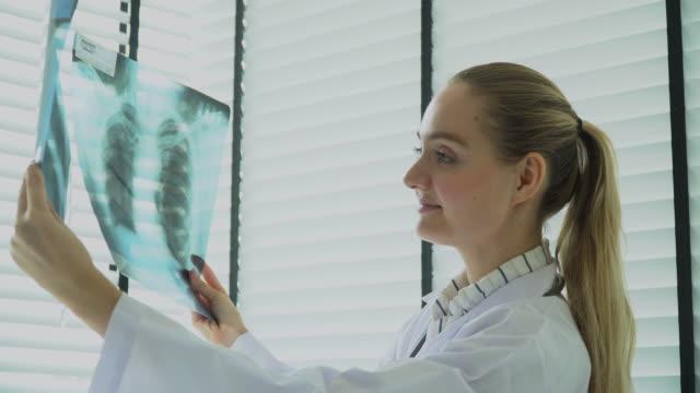 vídeos de stock, filmes e b-roll de médico fêmea que lê o raio x e que dá a consulta ao paciente - peito