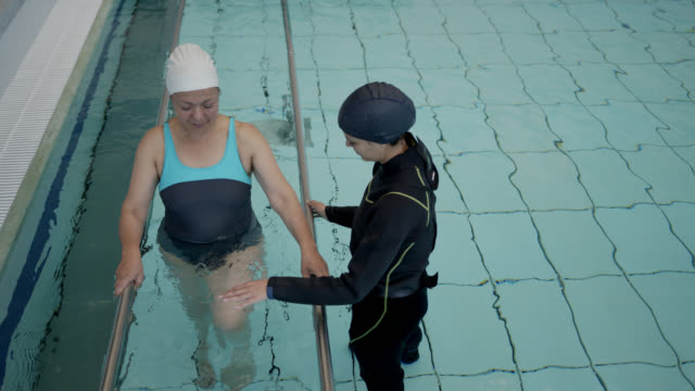female physiotherapist guiding female patient during hydrotherapy while she exercises her legs holding to parallel bars - hydrotherapy stock videos & royalty-free footage