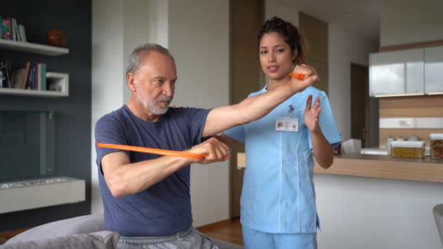 female physiotherapist helping a senior patient exercise at home - physiotherapy stock videos & royalty-free footage