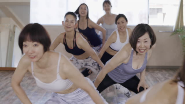 vídeos y material grabado en eventos de stock de female pilates instructor and pupil warming up before training - exclusivamente japonés
