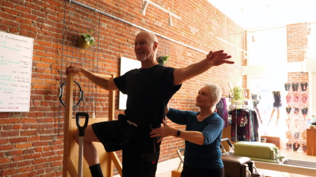 ms female pilates instructor assisting mature student on high-low chair during class in exercise studio - two people stock videos & royalty-free footage
