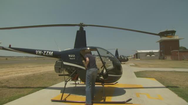 female pilot getting into robinson r22 helicopter, australia - 30 34 ��r bildbanksvideor och videomaterial från bakom kulisserna