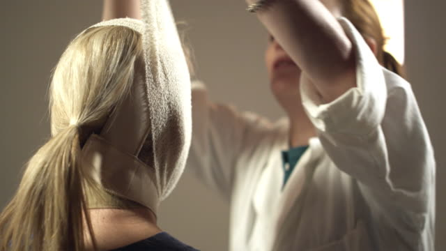 CU. R/F, Female plastic surgeon unwrapping facial bandages from patient looking into hand-held mirror, Sydney, Australia