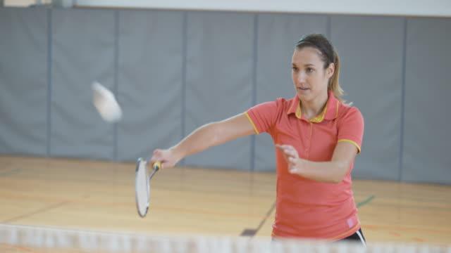 vídeos de stock, filmes e b-roll de feminino jogador jogando badminton indoor - badmínton esporte