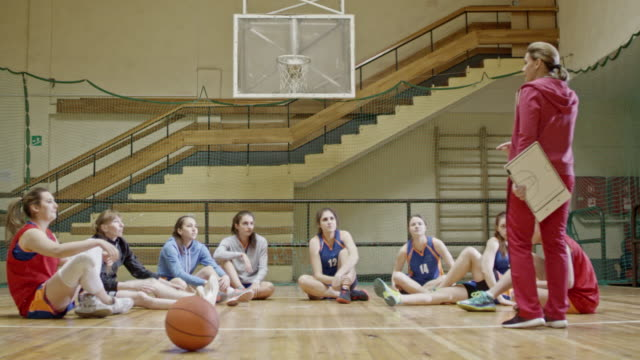 Female players listening to coach on basketball court