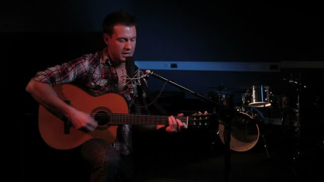 vídeos y material grabado en eventos de stock de mujer tocando la guitarra y canta en el estudio de grabación - objeto fabricado