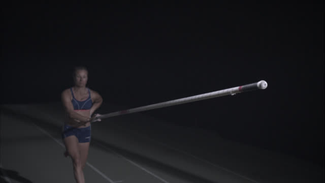 A female pole vaulter narrowly passes the bar.