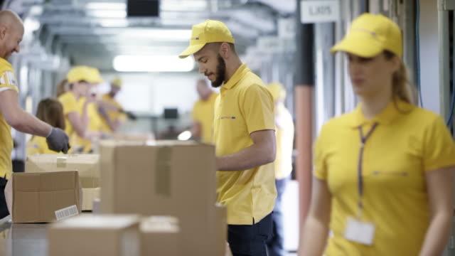 ds weiblich postarbeiter stepping auf dem förderband zu helfen, ihre männlichen kollegen die pakete sortieren - entladen stock-videos und b-roll-filmmaterial