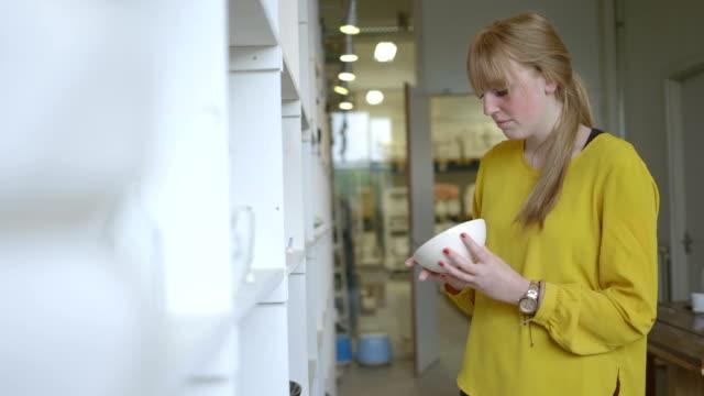 vídeos de stock e filmes b-roll de female potter checking pottery in workshop - só uma mulher de idade mediana