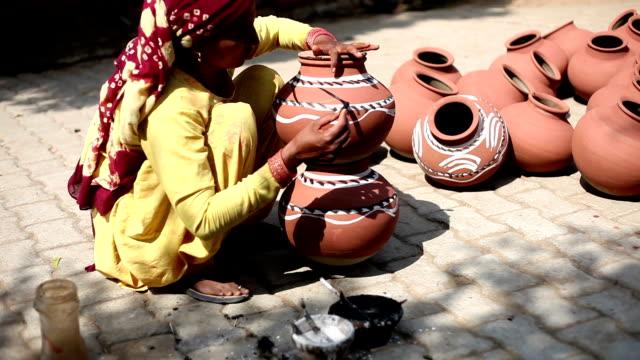 Female potter coloring pots