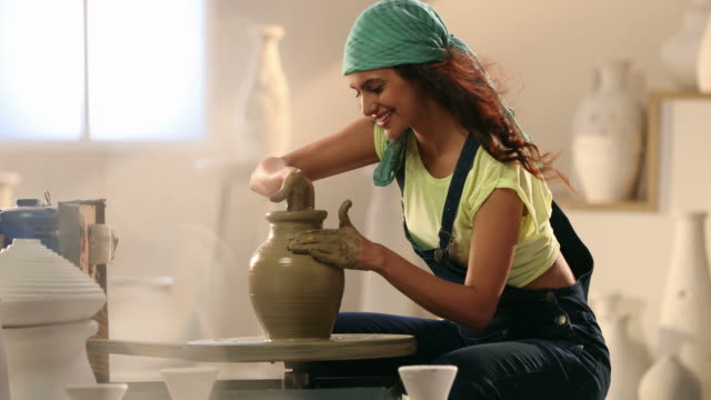 ms female potter shaping clay pot on pottery wheel in workshop / delhi, india - potter stock videos & royalty-free footage