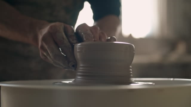 Female potter shaping pot on wheel