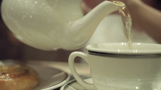 female pouring hot tea close up shot