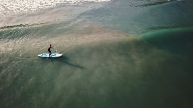 Female practice paddle boarding in the sea, view from drone