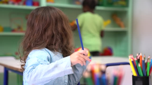 female preschool student coloring against friends - colored pencil stock videos and b-roll footage
