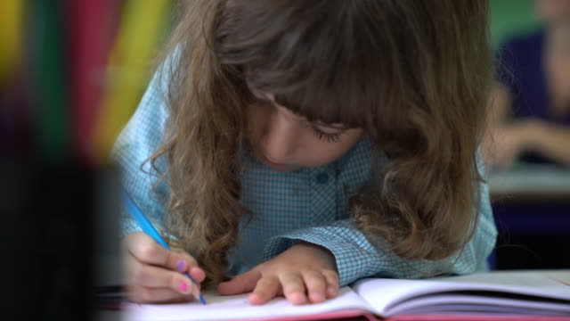 female preschool student coloring in book at desk - colored pencil stock videos and b-roll footage