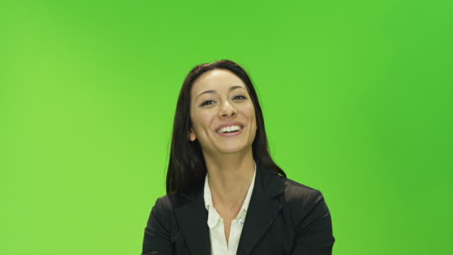 CU female presenter in front of green screen in TV studio, talking,  looking to camera