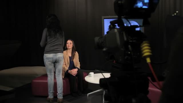 Female presenter receiving make up in studio