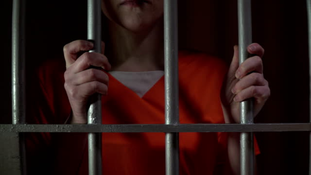 4K Female Prisoner in Jail Cell holding the bars