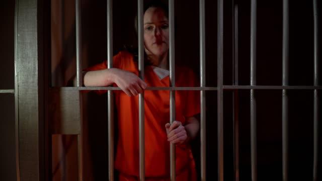 vídeos y material grabado en eventos de stock de 4 k reclusa en celda de la cárcel sostiene las barras - preso