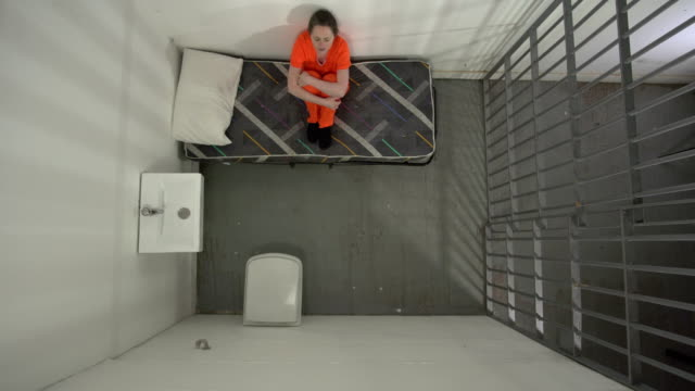 4K AERIAL: Female Prisoner in Jail Cell Sat on bed