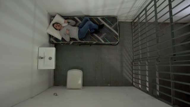4k antenne: weibliche gefangene in gefängniszelle, nicht schlafen - gefängnis stock-videos und b-roll-filmmaterial